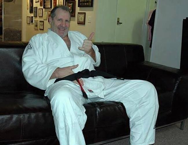 Ed O'neill in a BJJ gi doing his famous Al Bundy pose