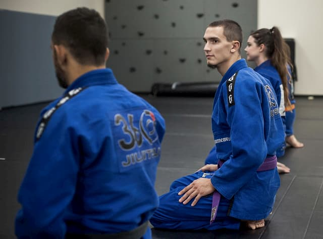 Students kneeling in a Jiu Jitsu class wearing BJJ gi