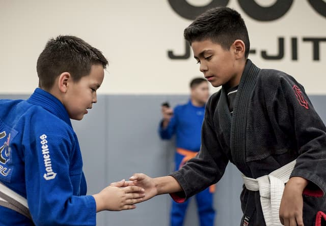 Two kids shaking hands before sparring jiu jitsu