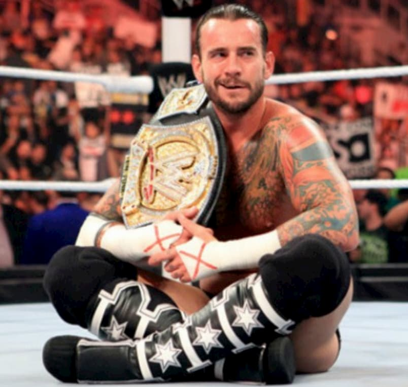 CM Punk posing in the ring with WWE belt