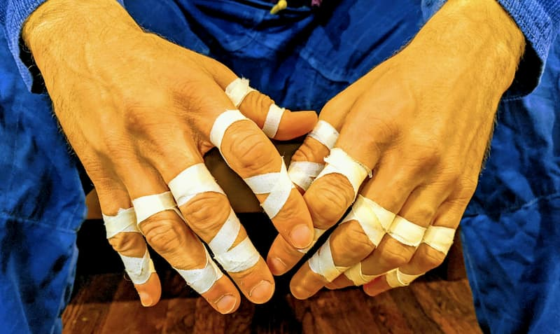 A BJJ practitioner's hands with tape on fingers
