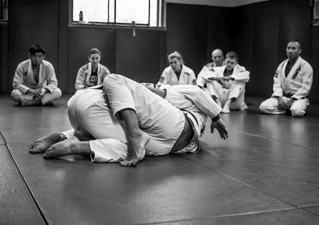 A group of people learning BJJ concepts