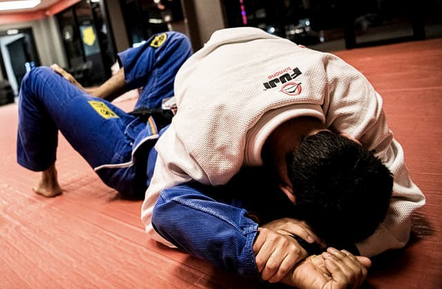 Two men training Jiu Jitsu and rolling