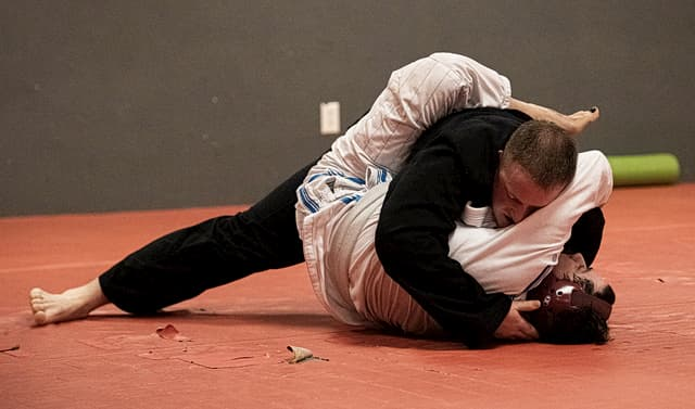 Two people rolling in Jiu Jitsu gis